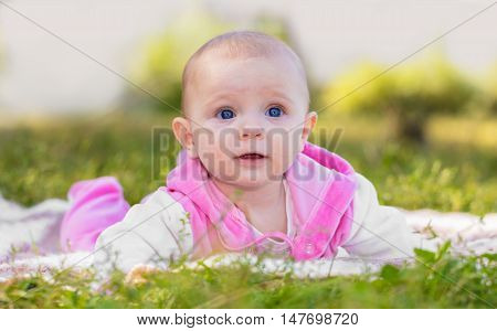 portrait of a smiling baby girl on the grass