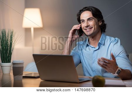 Good news. Happy handsome smiling young man speaking on cell phone and using laptop while sitting at the table.