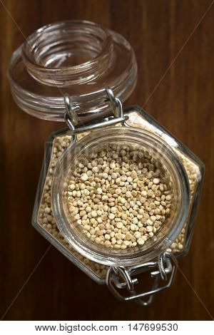 Raw quinoa grains (lat. Chenopodium quinoa) in glass jar photographed overhead on dark wood with natural light (Selective Focus Focus on the top of the quinoa)