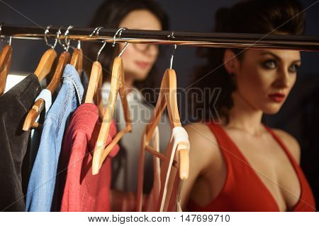 Talented stylist is helping model to wear new dress. Women are standing backstage. Focus on trendy clothes hanging on rack