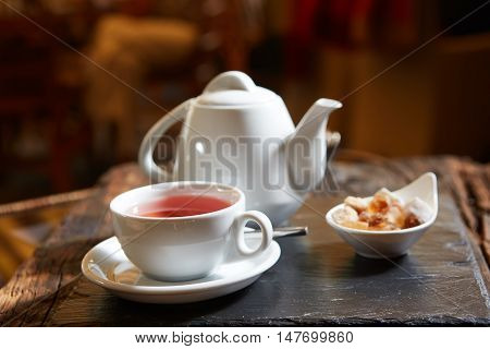 white teapot with tea Cup, saucer and teaspoon.