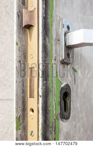 Old metal door with a lock case and cylinder