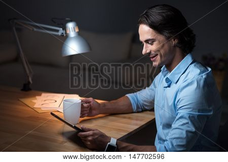 Great work . Smiling concentrated young man sitting at the table and holding cup of tea while using tablet.