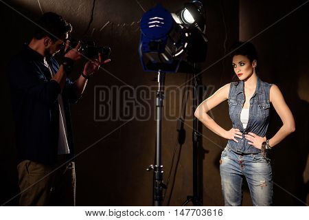Professional male photographer is shooting young model. He is standing and holding camera near his face. Confident woman is posing with arms akimbo
