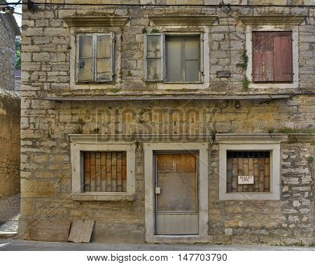 An historic old derelict building in Skradin old town Sibenik-Knin County Croatia. The sign on the window announces that the building is for sale.