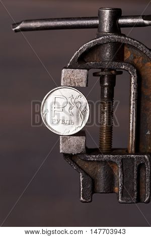 Weakening of the russian ruble concept. Coin in old vise