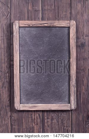 Rustic menu blackboard on wooden wall with copy space