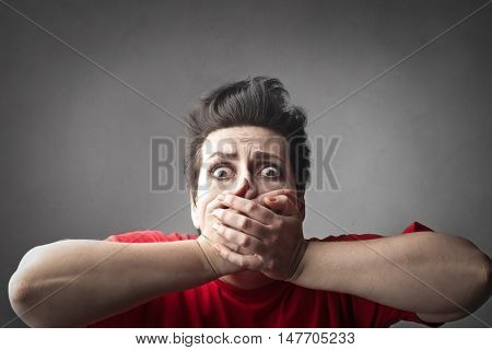 Scared woman covering her mouth with her hands