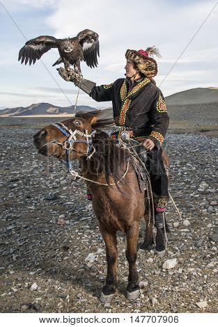 Bayan Ulgii Mongolia September 30th 2015: Mongolian eagle hunter with his eagle and horse