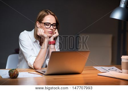 Involved in work. Pleasant concentrated beautiful woman sitting at the table and using laptop while working