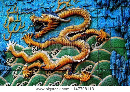 Beijing China - May 2 2005: Tile bas relief dragon spewing fire on the Screen of Nine Dragons in the Forbidden City