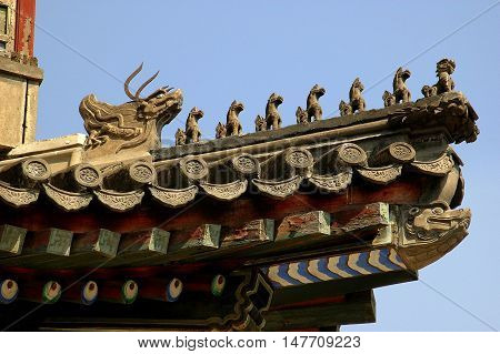 Beijing China - May 4 2005: Row of glazed ceramic dragons line a flying eave roof atop the Great Stage in the 1891 Garden of Virtue and Harmony at the Summer Royal Palace