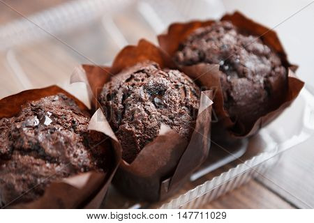 Three Chocolate Muffins In Plastic Container