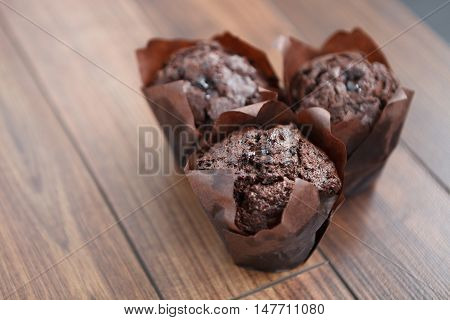 Three Delicious Chocolate Muffins On Wooden Table