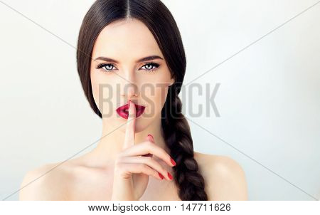 Beautiful  brunette model girl with  long braid hair . Hairstyle  pigtail  . Red lips and nails manicure .Woman  holds a finger on her mouth a secret poster