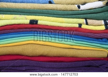 close up of a colorful stack of folded clothes texture background