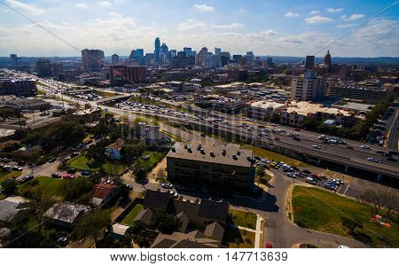Urban Sprawl Cityscape Skyline with I-35 Interstate highway busy traffic moving on a sunny day in Summer growing city downtown aerial photography