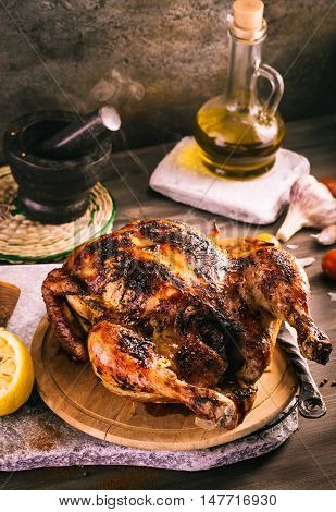 Whole roasted chicken on old rustic table