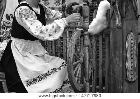 Near an old spinning wheel sits a young woman in national costume and produces yarn. Black-and-white photo.