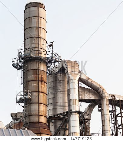 Silos ,staircase and smokestacks of a factory.