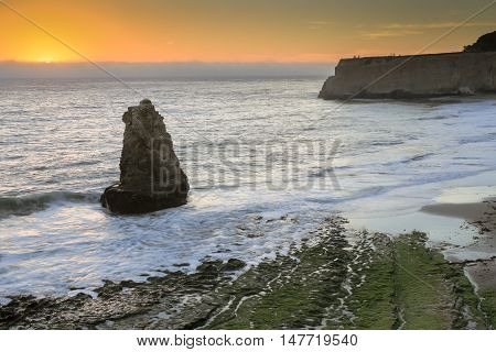 Pacific Ocean sunset from San Vicente Creek, Davenport, California, USA. Davenport rugged yet beautiful Coastline overlook windswept, where translucent waves crash against the rustic California ledge.