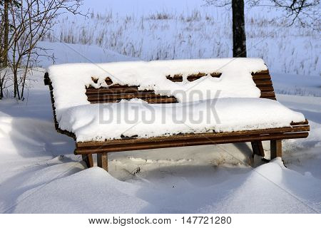 View of the wooden bench in the snow