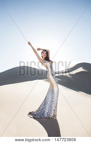 Professional photo shoot in a desert. Beautiful sexy asian woman model in luxury shiny dress in a desert