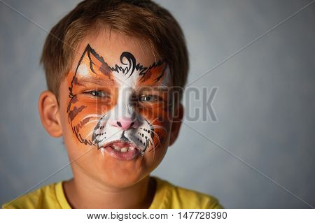6 years old boy with blue eyes with face painting of a cat or a tiger. Orange.