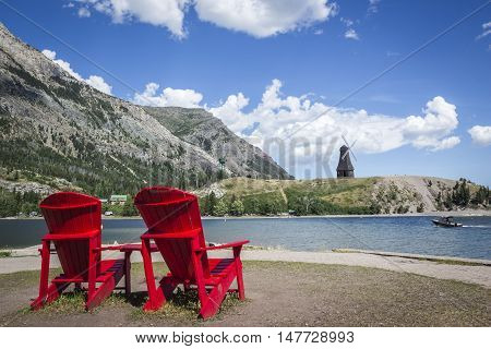 horizontal image of two dark red wooden lawn chairs sitting in the forefront facing the lake with a boat floating by flanked by mountains on a warm summer day.