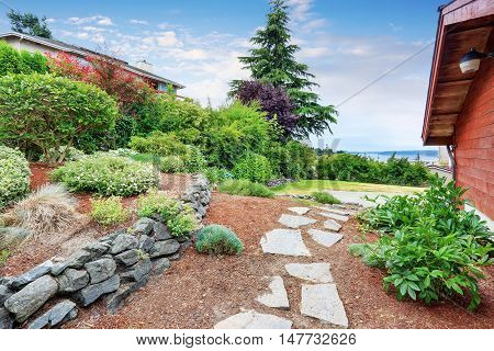 Well Kept Garden Near The House With Wooden Trim. Nice Landscape Design.
