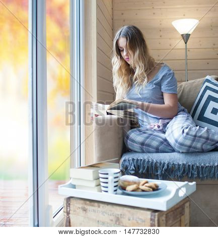 Young beautiful blonde woman with cup of coffee sitting home relaxing by the window reading book wearing pajamas.  Blurred garden fall background. Lazy day off concept.