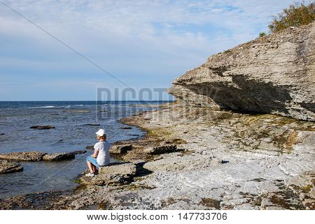 Woman sitting by a cost with eroded limestone cliffs