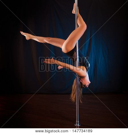 Young sexy girl pole dance shows. Extreme stunts on a pole dance. Studio shot on dark background young woman pole dancer
