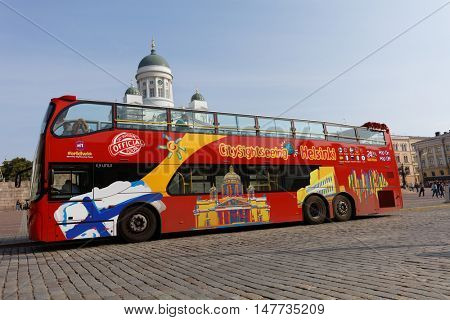 HELSINKI, FINLAND - AUGUST 21, 2016: Tourists in the sightseeing tour bus against the Helsinki Cathedral. Hop-On Hop-Off buses departs from Senate square every 20 minutes