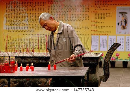 Chengdu China - September 20 2006: An elderly Chinese man lighting incense sticks from burning red candles at the Da Ci Buddhist Temple