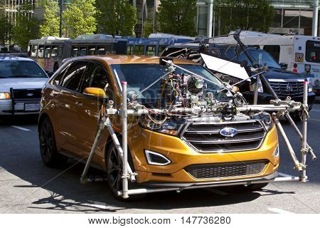 Vancouver, BC - April 20, 2015 - Gold, Ford movie car, fully loaded with camera and lighting equipment, escorted by Vancouver police car just behind it. Movie scene was being shot while driving on a busy downtown Vancouver street with cars, buses and buil