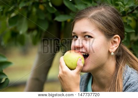 young girl holding green apple, eating it