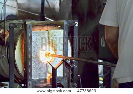 Vancouver, BC - April 20, 2015 - Glass blower, partial arm and body, turning a peice of glass in a molten hot kiln on Granville Island. Small shop keeps alive the art of hand draw glass blowing and demonstrates the art in a see through glass enclosure. Al