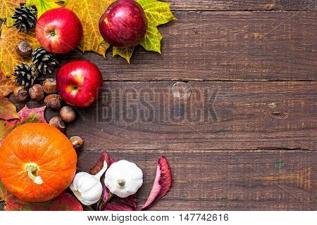 harvest or thanksgiving background with autumnal fruits and vegetables with autumn leaves on wooden board