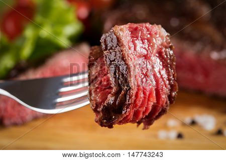 medium-rear steak grilled on the wooden background
