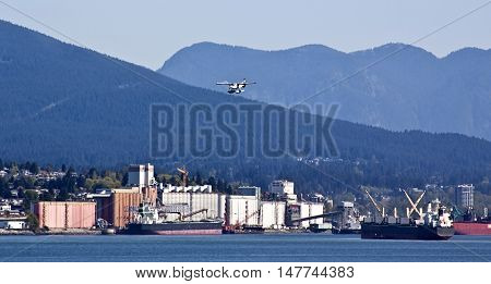 Seaplane coming in for a landing in Vancouver Harbour (harbor) on a sunny day with blue cloudless sky. View of West Vancouver docks yards, businesses, cargo ships in the harbor and the Rockies in the background