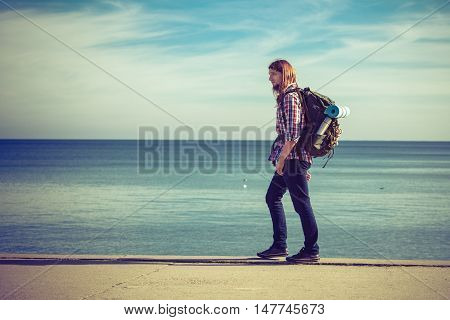 Man hiker backpacker walking with backpack by seaside at sunny day. Adventure summer tourism active lifestyle. Young long haired guy tramping