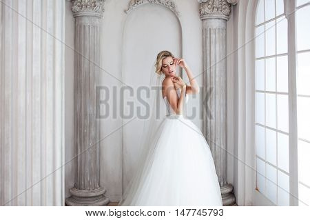 Charming young bride in luxurious wedding dress near the window. Pretty girl, photo Studio