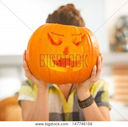 Housewife Holding A Big Jack-o-lantern Pumpkin In Front Of Head