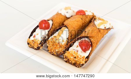 Three Sicilian cannoli with ricotta and pieces of candied pumpkin on the white plate