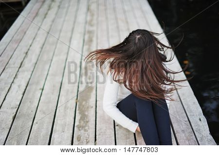 Young girl with flying in the wind the hair on the wooden bridge near the lake