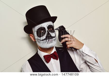 a man with calaveras makeup, wearing waistcoat, bow tie and top hat, with a black crow in his shoulder