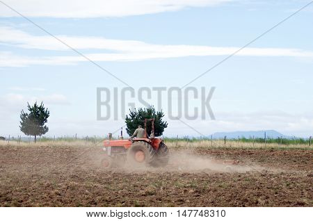 Red Tractor Ploughing Field