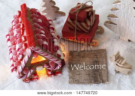 Label With English Text Welcome. Gingerbread House On Snow With Christmas Decoration Like Trees And Moose. Sleigh With Christmas Gifts Or Presents.