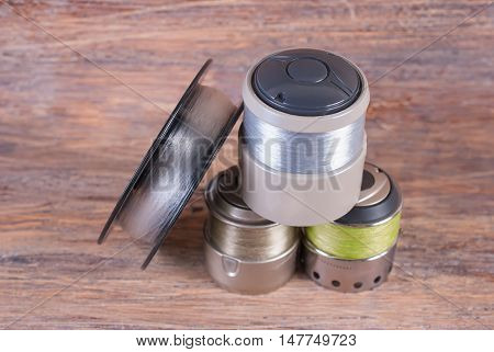 Spool spool wound with a fishing line. Wooden background